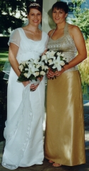 Brides wedding dress: Empire waist line dress in soft ivory satin and ivory georgette split on front forming a train. Bridesmaid: Gold and cream brocade halter bodice, and gold raw silk look gold shantung 'Bell' skirt.