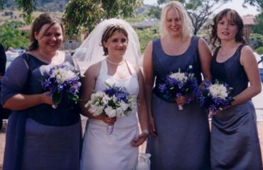 A Bride with bridesmaids. The bride here has a boned 'V' neckline brocade bodice with a halter, and bell skirt. Her bridesmaids have round neckline bodices in a pewter purple brocade with matching bell skirts of delustered satin, one wears a chiffon wrap.